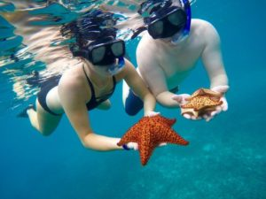 Couples with a star fish during a punta cana snorkeling excursion