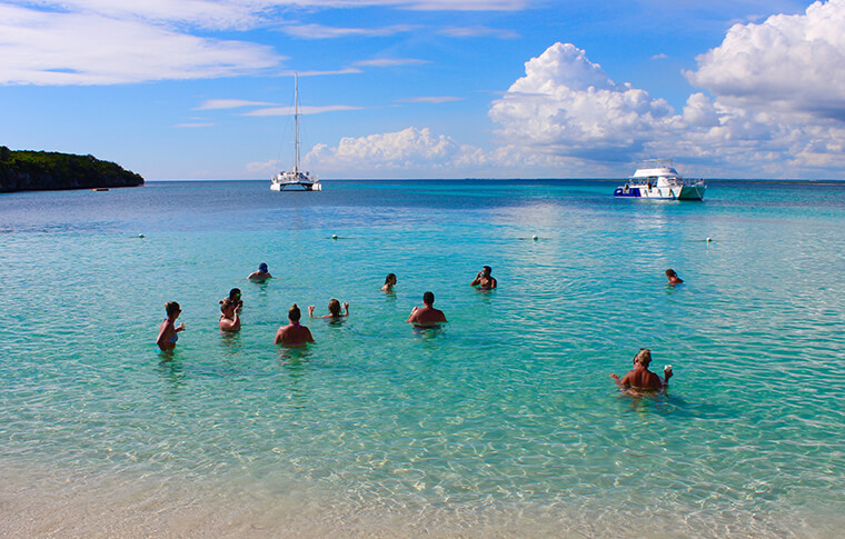 Group of people swimming in the shallows of a nice beach