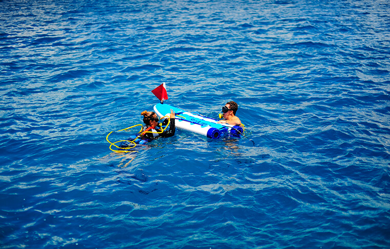 2 snorkelers with inflatable raft out on the water