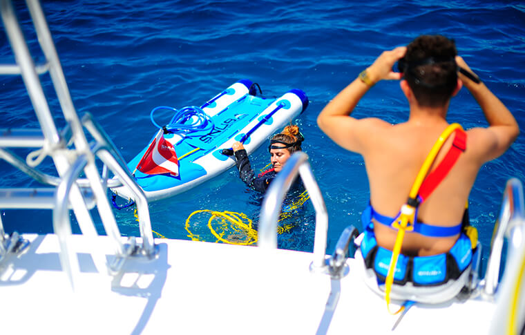 Snorkeler in the water with inflatable raft with person waiting to jump in the water from the boat