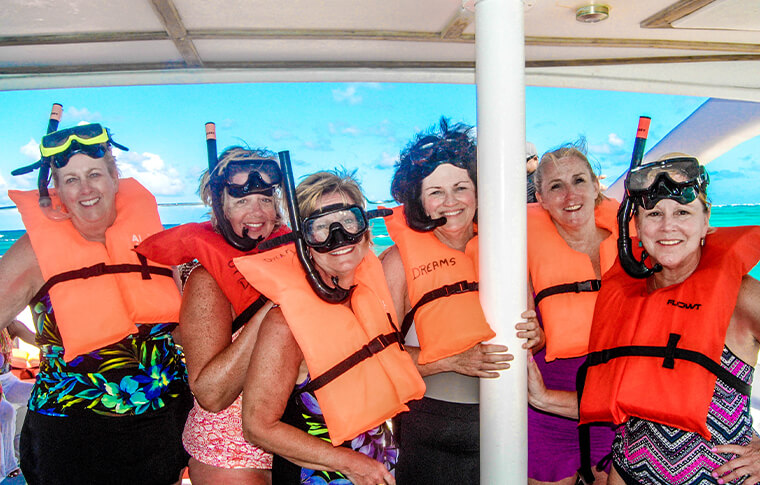 People onboard a boat with snorkel gear on ready to go