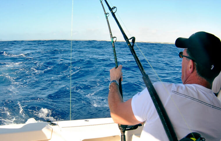 Person fishing in the ocean reeling in something