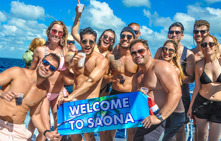 Group of people holding a banner reading'welcome to saona'