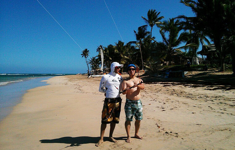Instructor and student watching kite surf high in the air while standing on the beach