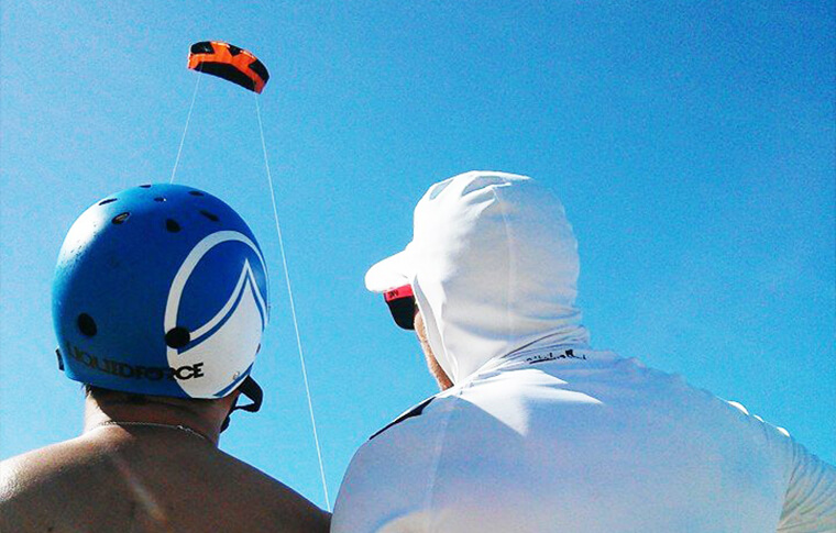 Instructor and student watching kite surf high in the air