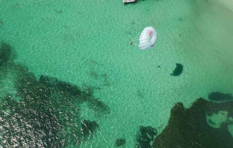 Ariel view of a parasail flying over the clear green