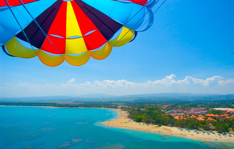 Colourful parasail flying in the air above the beautiful Caribbean coast