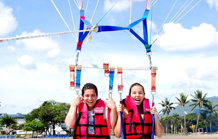 2 people strapped into a parasail ready for take off