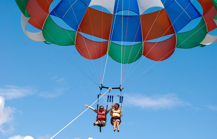 2 people strapped in a parasail high in the air