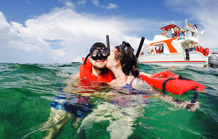 2 snorkelerson the surface with one kissing the cheek of the other
