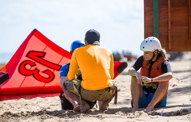 Instructor and 2 students on the beach learning how to kite surf