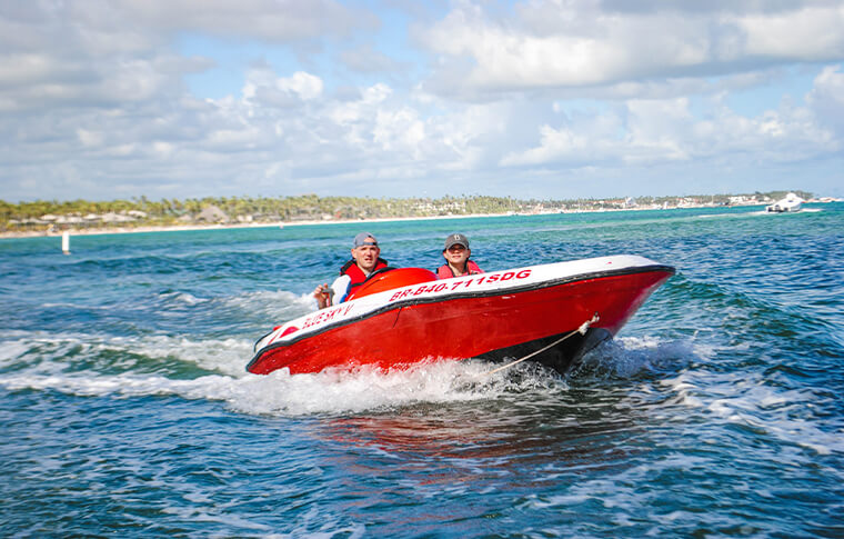 2 people driving a small speed boat in a beautiful tropical bay
