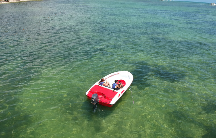 Speedboat sitting in the water with 2 people on board