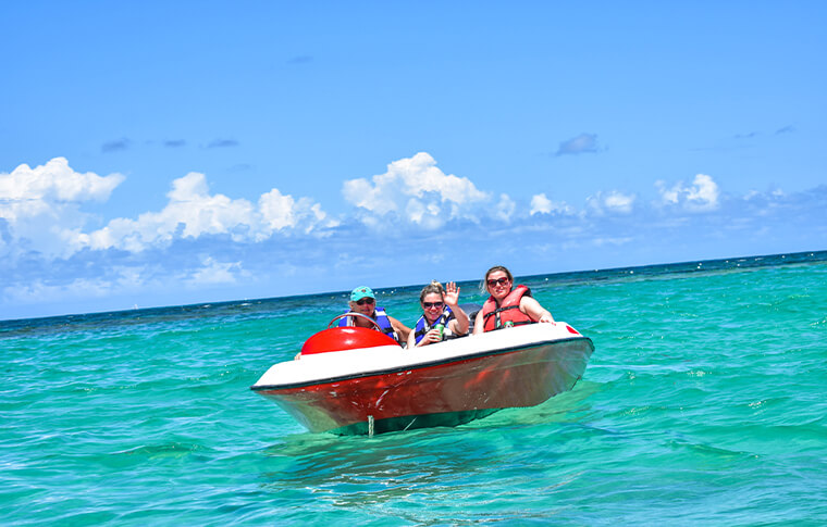 3 people driving a speed boat on the beautiful blue sea