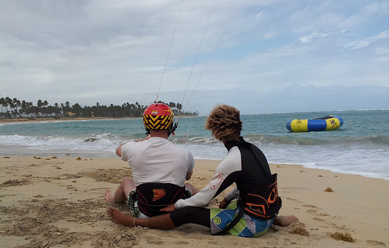 Instructor and student on the beach learning how to kite surf
