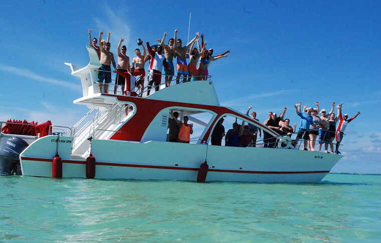 Small white boat packed with people with arms raised dancing