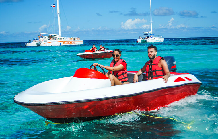 2 people driving a speedboat with catamerans in the background