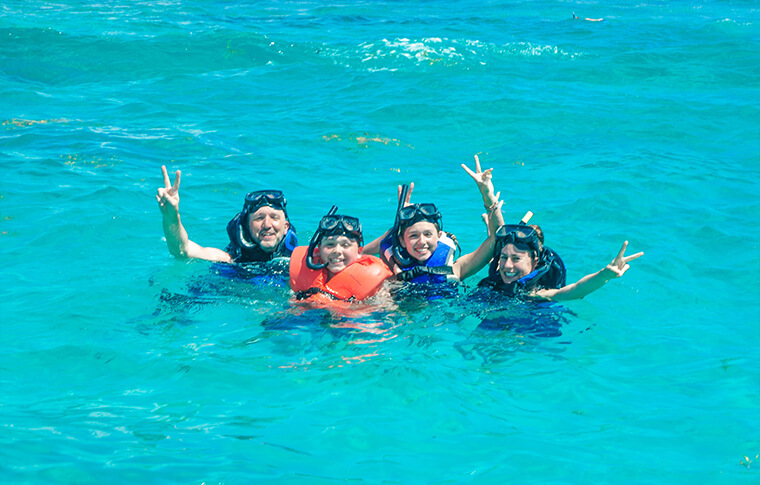 4 people with vests and snorkels waving at the camera in the water