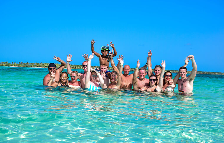 Big group of people shallow swimming with hands in the air