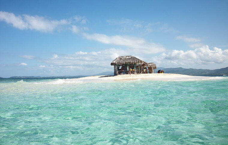 Small wooden hut on a tiny island surrounded by white sand and crystal blue water