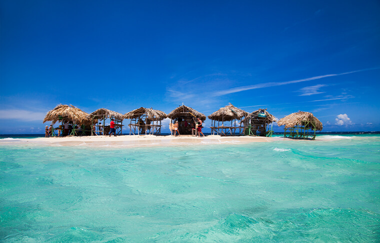 Small wooden huts on a tiny island surrounded by white sand and crystal blue water