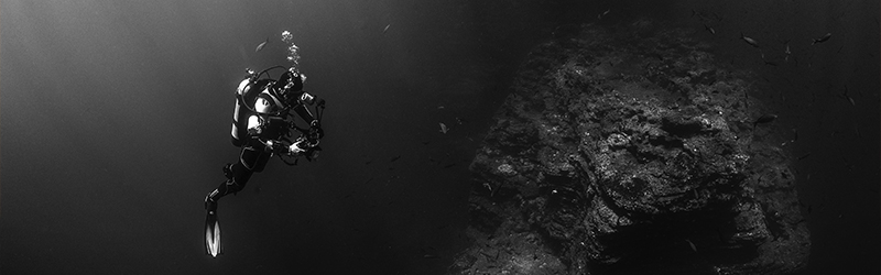 black and white image of diver at night next to underwater wall