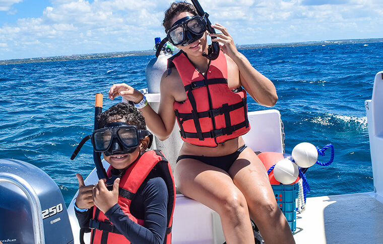 2 snorkelers on the boat ready to jump in the water