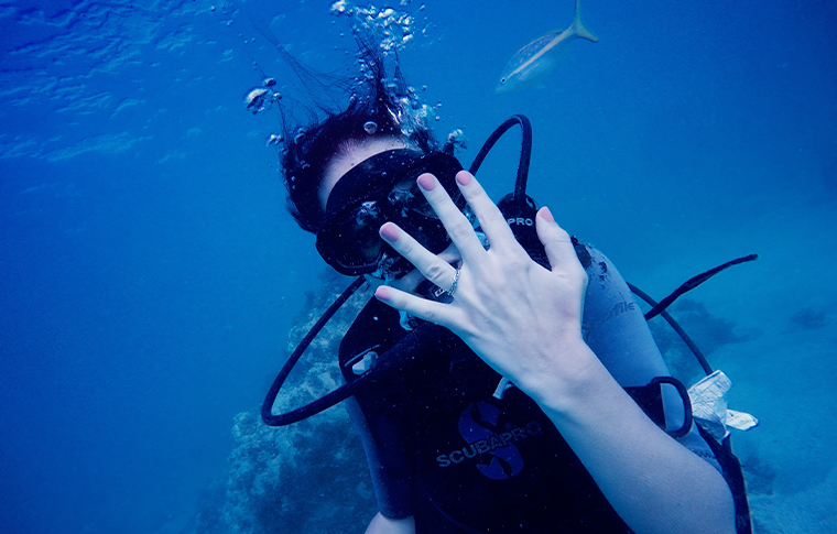 Diver holding engagement ring up to camera underwater