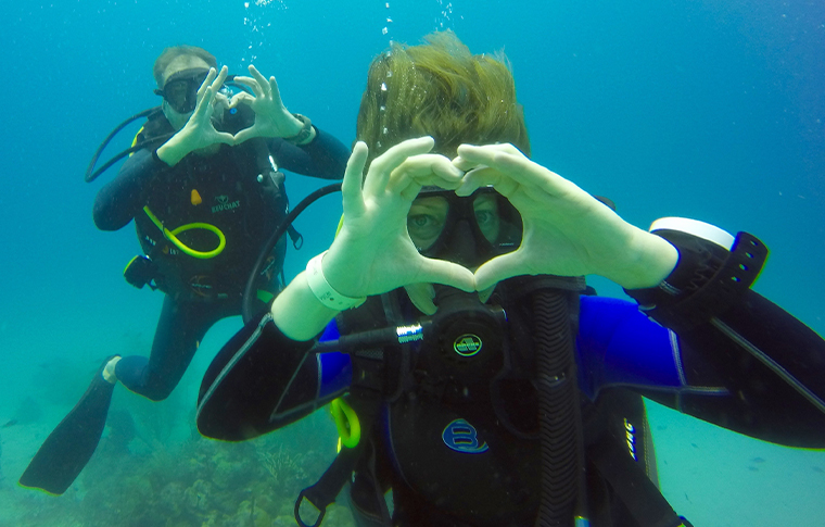 Scuba divers underwater making heart shape with hands