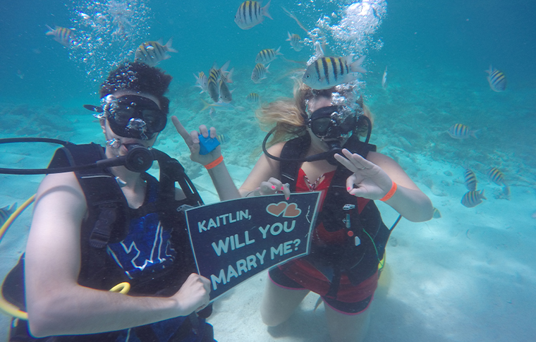 Divers underwater with sign that reads - will you marry me?