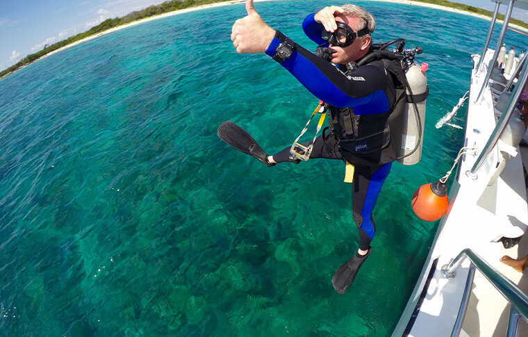 Diver with full equipment jumping into water with thumb up