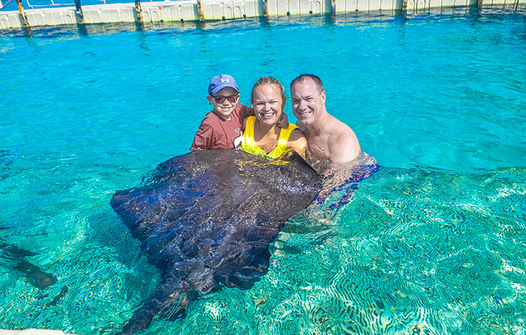 Family holding a stingray in the shallow turquoise water