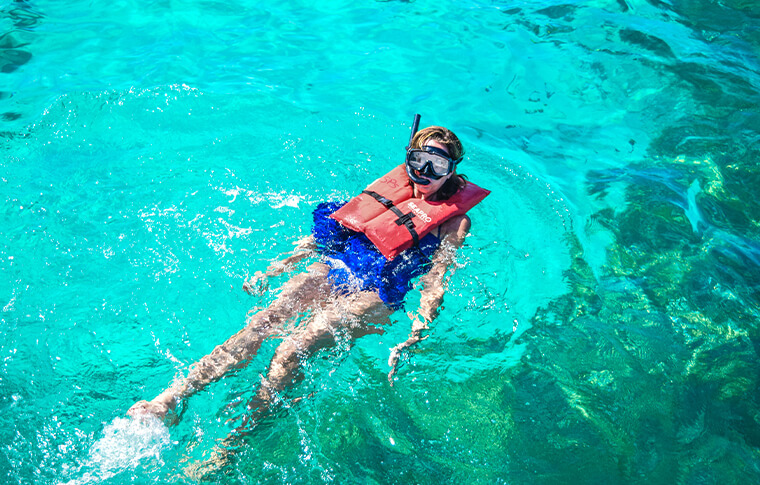 Snorkeler on their back with life vest paddling along the surface
