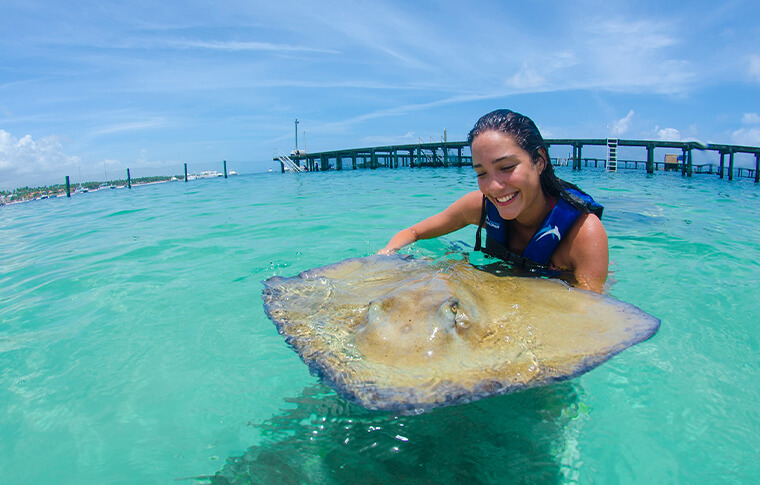 oamn holding a stingray with big smile on her face
