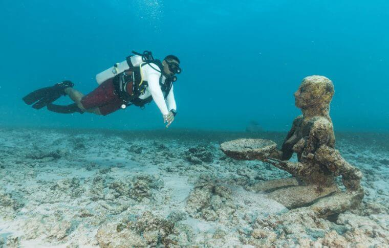 Scuba diver floating next to an underwater statue of a person